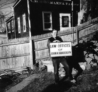 1980 the late Mattie Fairweather, electrician, holding Vanderlyn law office sign from early 1900s.